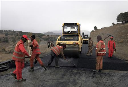 A military soldier stands near labourers working on the construction of the Wana Jandola road in Wana, in Pakistan's South Waziristan tribal region bordering Afghanistan